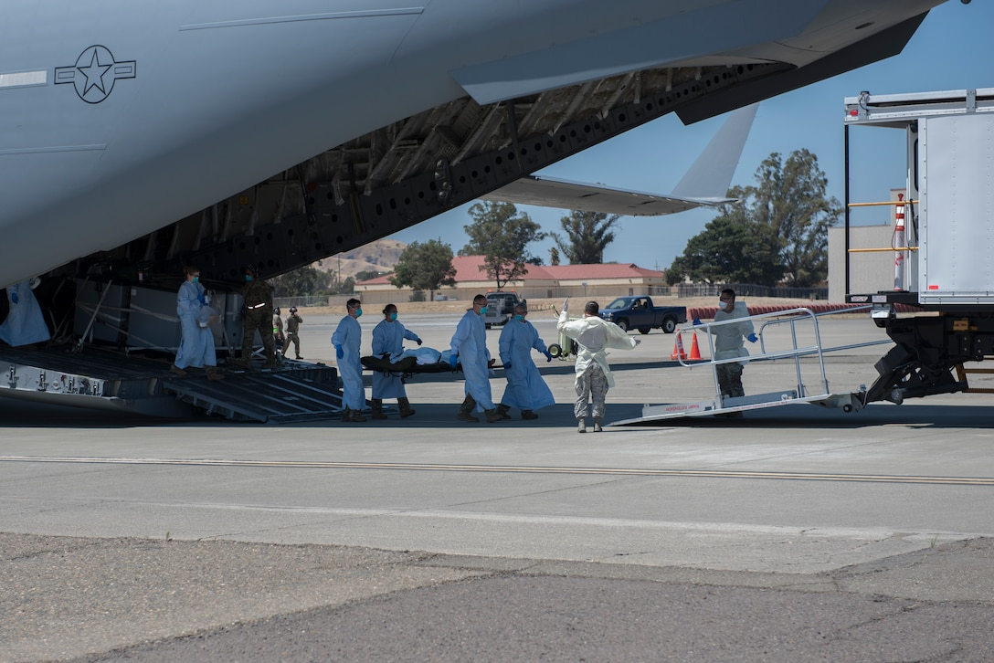 U.S. Air Force Airmen from the 775th Expeditionary Aeromedical Evacuation Flight offload a COVID-19 positive patient from a C-17 Globemaster III July 17, 2020 at Travis Air Force Base, California. Travis Airmen transported the patient from the Indo-Pacific Command area of responsibility as part of the Air Force's response to the COVID-19 outbreak. This transport marked the Air Force's first TIS mission into the INDOPACOM AOR and the 18th time employing TIS units to transport COVID-19-positive passengers. (U.S. Air Force photo by Airman 1st Class Cameron Otte)