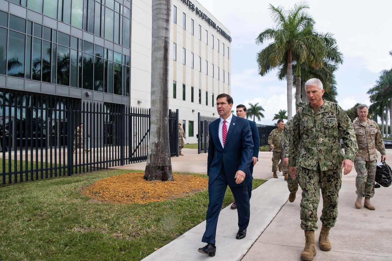 Two men, one in a Navy uniform, walk on the sidewalk past a building.