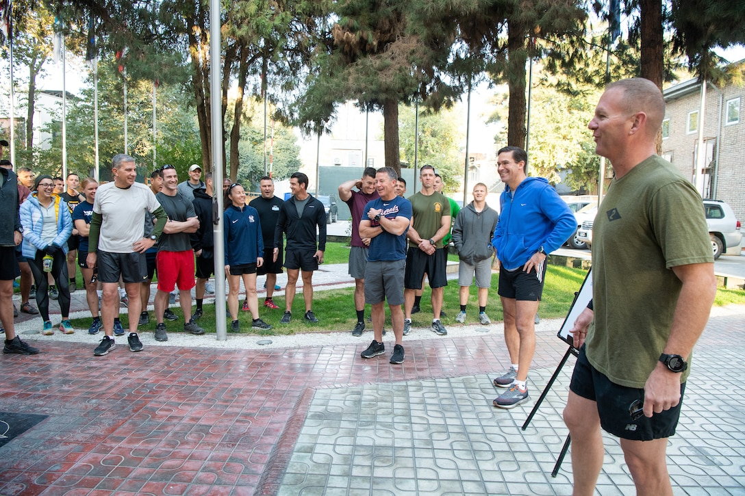 Men and women in PT outfits ready for training.