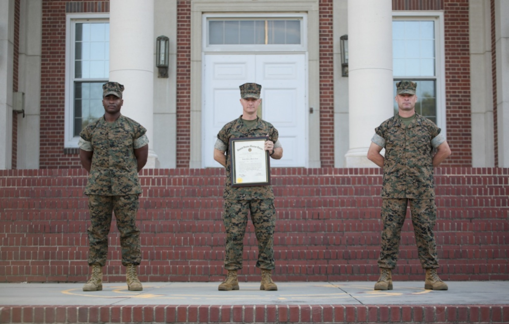 Master Sgt. Justin Gregory stands with his recruiter Master Gunnery Sgt. Dinky Byers and senior drill instructor Master Gunnery Sgt. Doug Mrusek after Gregory's promotion on Marine Corps Recruit Depot Parris Island S.C. July 1, 2020.