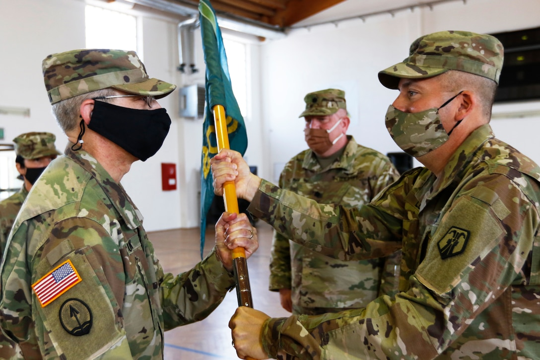Col. Douglas LeVien, right, passes the unit colors to Lt. Col. Frank Suyak, incoming commander of the 209th Digital Liaison Detachment during a change of command ceremony July 19, 2020 in Wackernheim, Germany. The detachment, headquartered at U.S. Army Garrison Wiesbaden, is part of the U.S. Army Reserve's 7th Mission Support Command and serves in direct support of U.S. Army Europe.  (U.S. Army Reserve photo by Staff Sgt. Chris Jackson/Released)