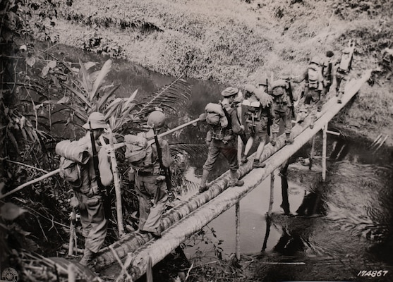 Soldiers with Company L, 3rd Battalion, 128th Infantry, 32nd Division, cross a creek between Warisota Plantation and Borio, New Guinea, Nov. 17, 1942.
