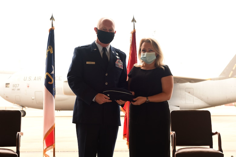 U.S. Air Force Brig. Gen. Allan R. Cecil (left), North Carolina National Guard (NCNG) Chief of Staff, is presented his new cover with rank emblem by Amanda Fox during Brig. Gen. Cecil's promotion ceremony at the North Carolina Air National Guard Base, Charlotte Douglas International Airport, July 18, 2020. Family, friends, and guard members gather to watch Col. Cecil pin on the rank of Brigadier General.