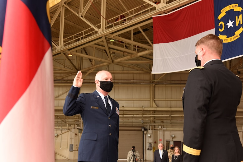 U.S. Army Maj. Gen. M. Todd Hunt (right), the Adjutant General of North Carolina National Guard (NCNG), leads U.S. Air Force Brig. Gen. Allan R. Cecil (left), NCNG Chief of Staff, in the reaffirmation of oath during Brig. Gen. Cecil's promotion ceremony at the North Carolina Air National Guard Base, Charlotte Douglas International Airport, July 18, 2020. Family, friends, and guard members gather to watch Col. Cecil pin on the rank of Brigadier General.