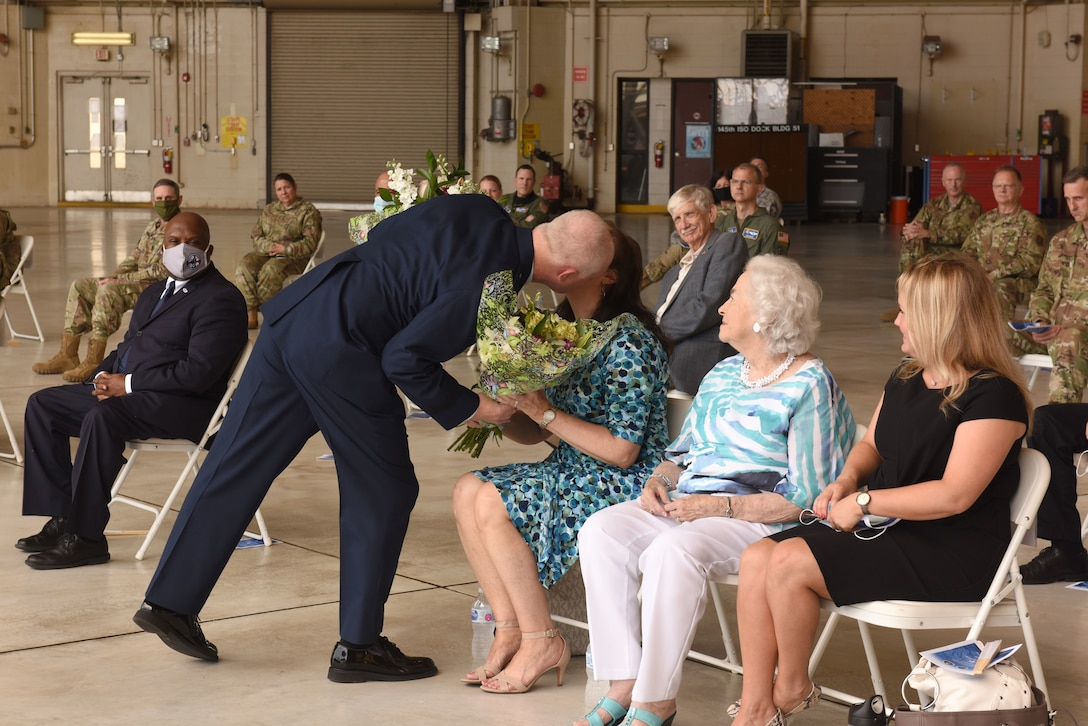 U.S. Air Force Brig. Gen. Allan R. Cecil, North Carolina National Guard (NCNG) Chief of Staff, gifts his wife, Jane, a bouquet of flowers as a token of his appreciation for her love and support over the years during his promotion ceremony at the North Carolina Air National Guard Base, Charlotte Douglas International Airport, July 18, 2020. Family, friends, and guard members gather to watch Col. Cecil pin on the rank of Brigadier General.