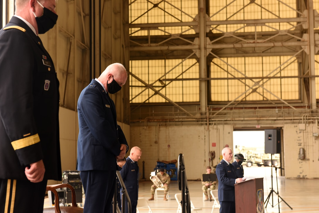 U.S. Air Force Chaplain, Lt. Col. Jeffrey Kidd (right), gives a closing prayer during the promotion ceremony of U.S. Air Force Brig. Gen. Allan R. Cecil (center), North Carolina National Guard Chief of Staff, held at the North Carolina Air National Guard Base, Charlotte Douglas International Airport, July 18, 2020. Family, friends, and guard members gather to watch Col. Cecil pin on the rank of Brigadier General.