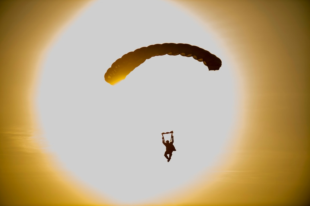 A soldier, shown in silhouette against an orange sky, parachutes with the sun in the background.