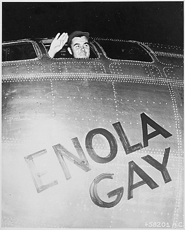 A man waves from the window of a B-29 bomber.
