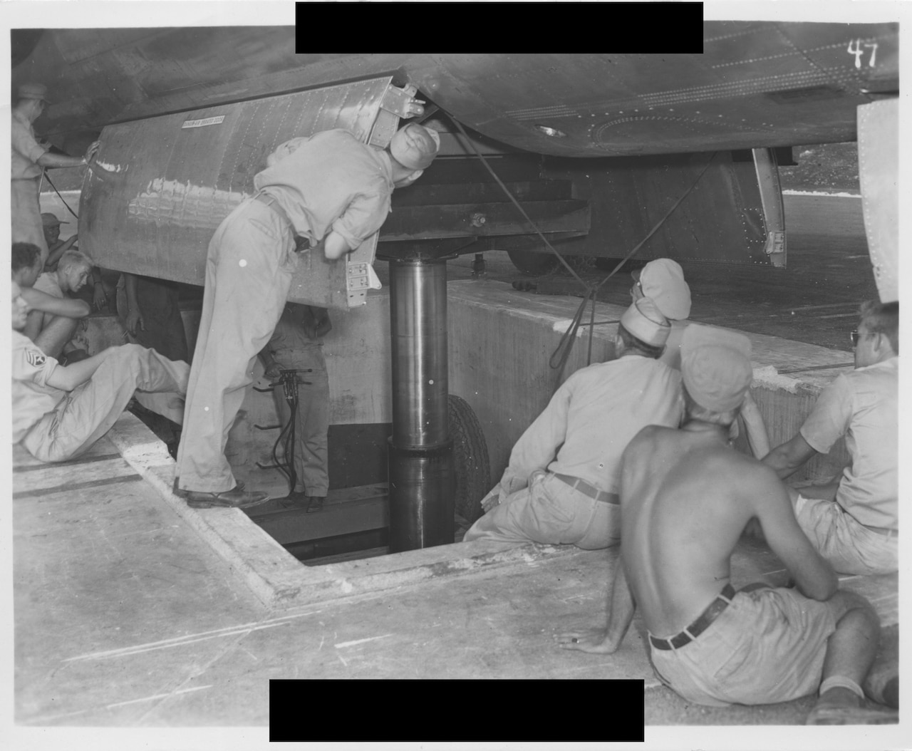 Several men look into the belly of an open airplane.