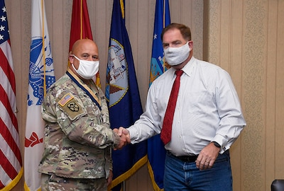Col. Bondy and DLA Disposition Services Director Mike Cannon shake hands while both wear mask.