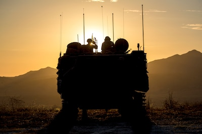 Marines are perched atop an amphibious assault vehicle, shown in silhouette, with mountains and an orange sky as the backdrop.