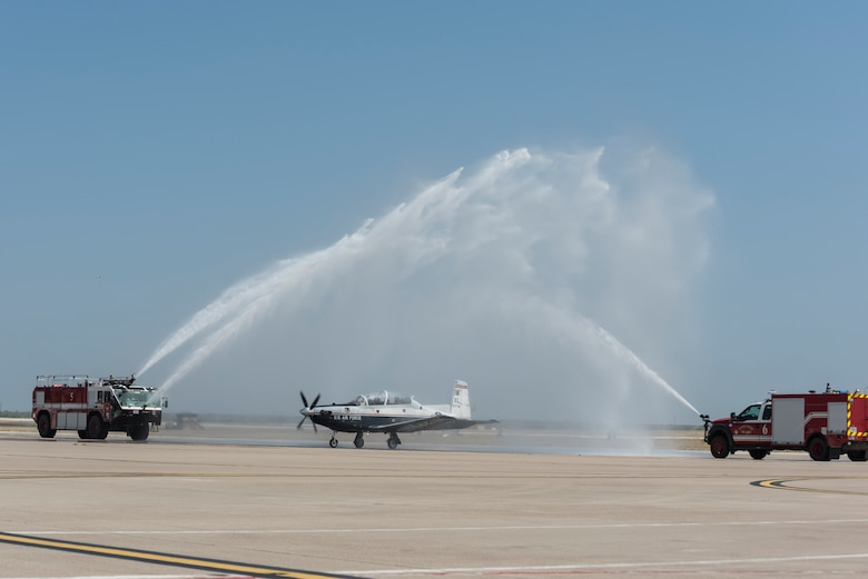 Col. Lee Gentile, 47th Flying Training Wing commander, ends his fini flight by taxiing under the arch of water, July 17, 2020 at Laughlin Air Force Base Texas. He parked in front of the base operations building where he was greeted by family, friends and co-workers to celebrate his last flight as an Air Force officer. (U.S. Air Force photo by Senior Airman Anne McCready)