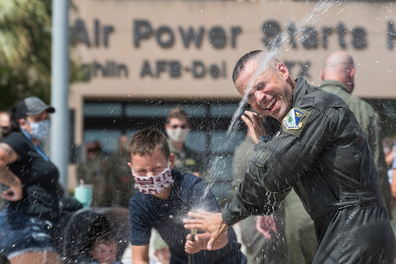 Col. Lee Gentile, 47th Flying Training Wing commander, is doused with water by his son, July 17, 2020 at Laughlin Air Force Base Texas. In celebration of a pilot's fini flight, it is tradition for his family to shower the pilot with water and champagne. (U.S. Air Force photo by Senior Airman Anne McCready)