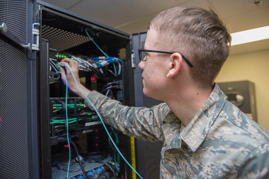 A young service member works on some information technology components.