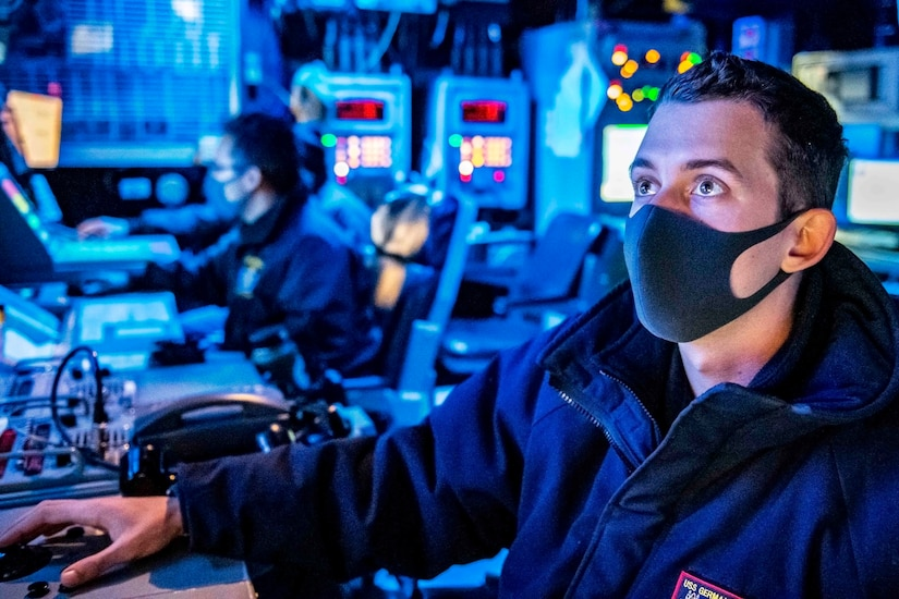 A sailor wearing a mask sits at a console in a blue-lit room.