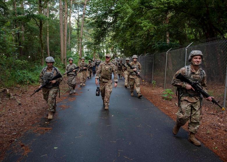 Airman Leadership School graduates ruck along perimeter road during the combat skills training course at Seymour Johnson Air Force Base, North Carolina, July 13, 2020.