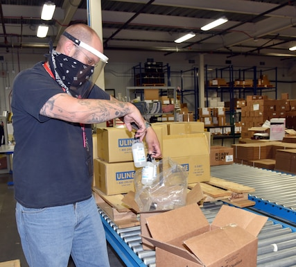 Male worker wearing face mask and face shield packs bottles into bags and boxes on a conveyor belt.