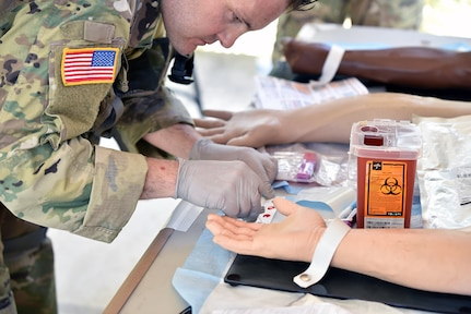 Staff Sgt. Ryan Morgan, 188th Medical Battalion, tests samples of blood to determine their type before preparing to draw whole blood for a simulated transfusion during the Best Medic lane.