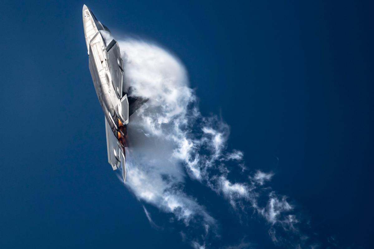 An Air Force jet creates a dramatic cloud burst as it turns in a blue sky.