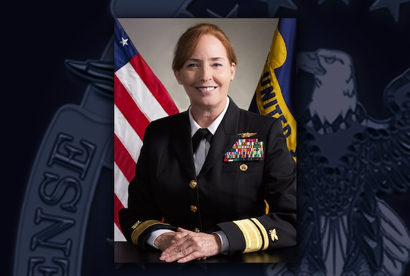 White woman in Navy dress blue uniform with ribbons