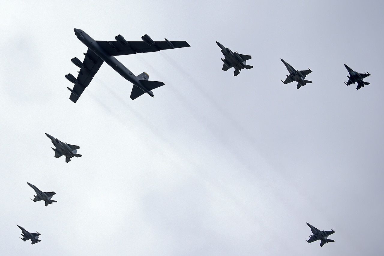 Aircraft from three nations fly in formation.