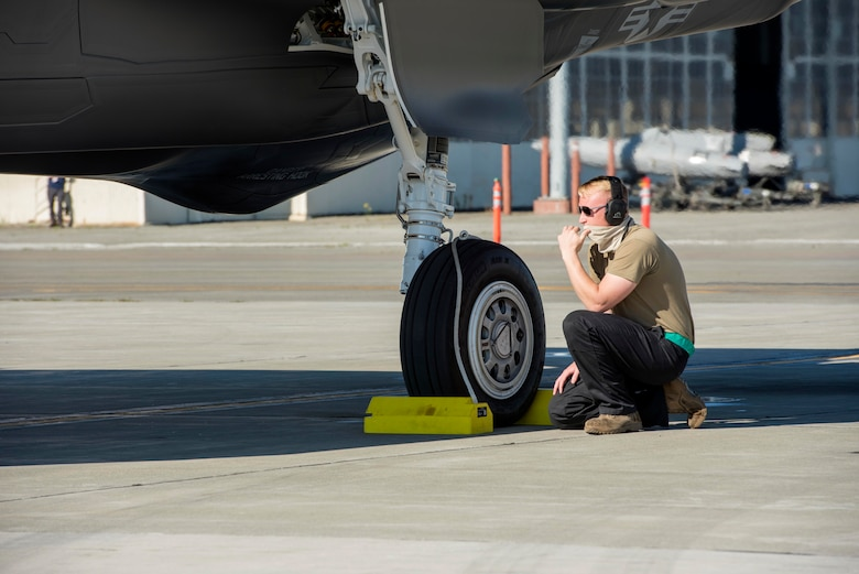 Tech. Sgt. Tyler Sherman, a 354th Aircraft Maintenance Squadron crew chief assigned to Eielson Air Force Base, Alaska, prepares to remove aircraft chocks from an F-35 Lightning II before takeoff at Joint Base Elmendorf-Richardson, Alaska, July 14, 2020.