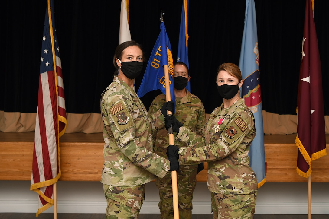 U.S. Air Force Col. Heather Blackwell, 81st Training Wing commander, takes the 81st Medical Group guidon from Col. Beatrice Dolihite, outgoing 81st MDG commander, during the 81st MDG change of command ceremony inside the Don Wiley Auditorium at Keesler Air Force Base, Mississippi, July 21, 2020. The passing of the guidon is a ceremonial symbol of exchanging command from on commander to another.. (U.S. Air Force photo by Senior Airman Suzie Plotnikov)
