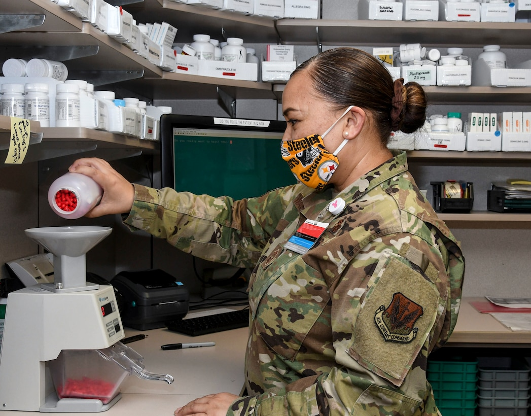 An airman pours pills into a scale.