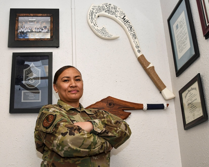 An airman stands for a photo in a room with framed items hanging on a wall.