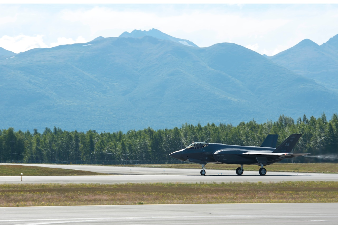 A military aircraft moves down a runway. In the background are mountains.