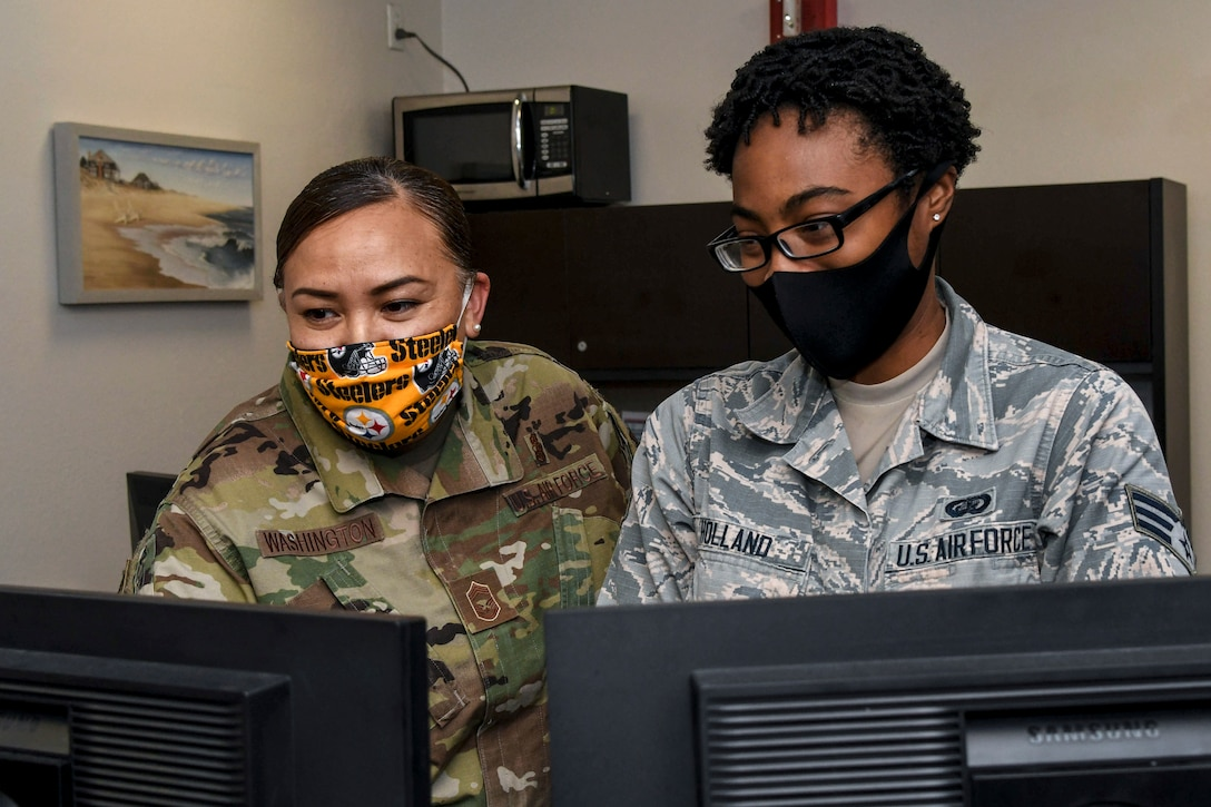 Two airmen look at computer screens.