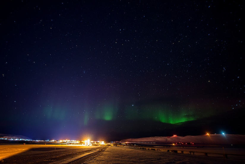 In a night sky, colored lights appear in the sky above a military installation.