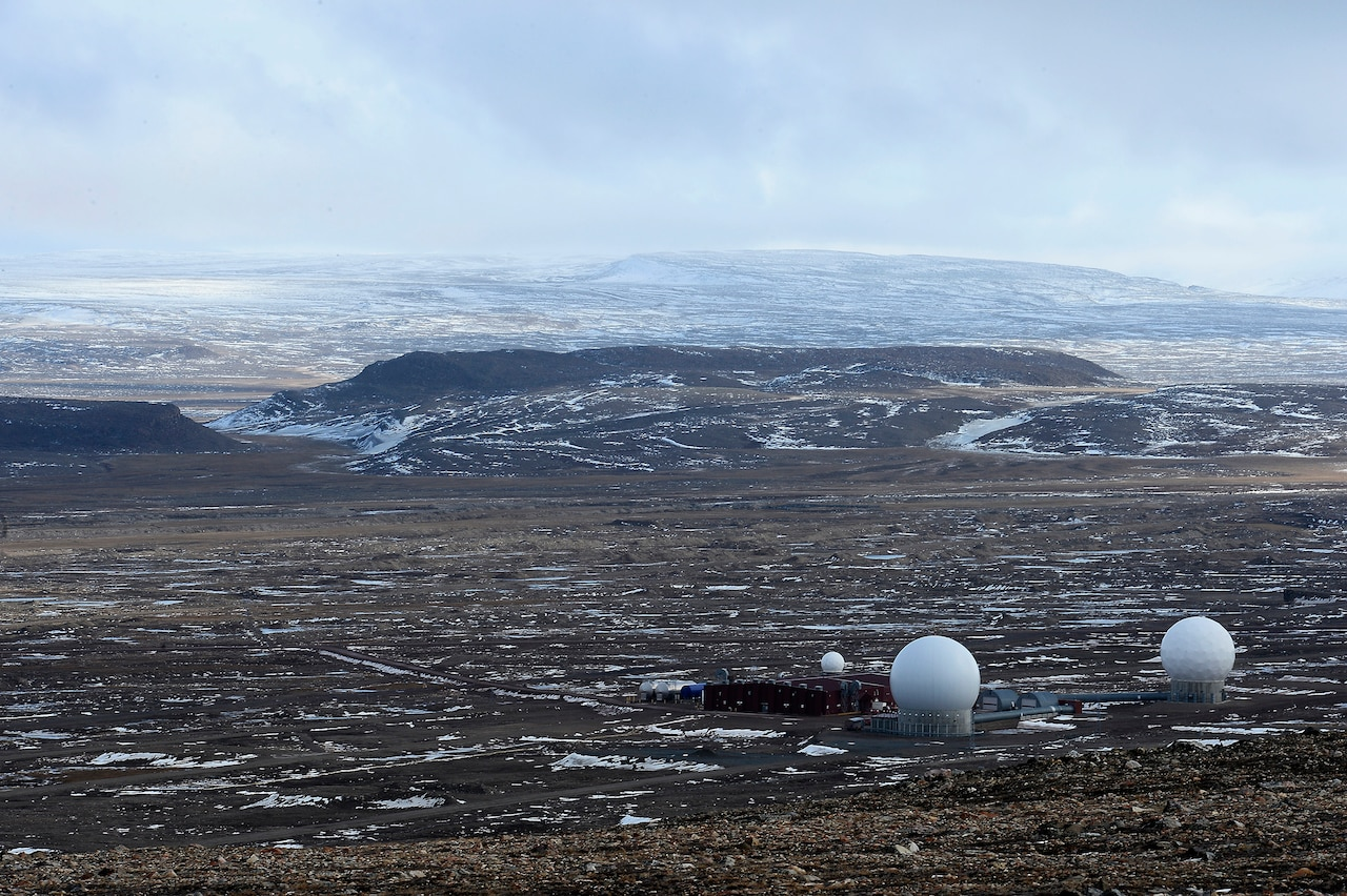 Golf-ball-like radar domes sit on a rocky, snowy landscape.