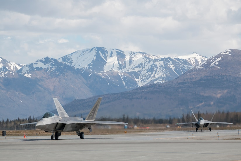 Military aircraft move down a runway. In the background are mountains.