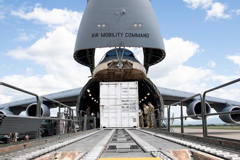 U.S. Airmen assigned to the 22nd Airlift Squadron, Travis Air Force Base, California, off-load a T6 container July 18, 2020, at Soto Cano Air Base, Honduras. The T6 container held 17,000 pounds of COVID-19 medical supplies for Honduras communities. (U.S. Air Force photo by Senior Airman Jonathon Carnell)