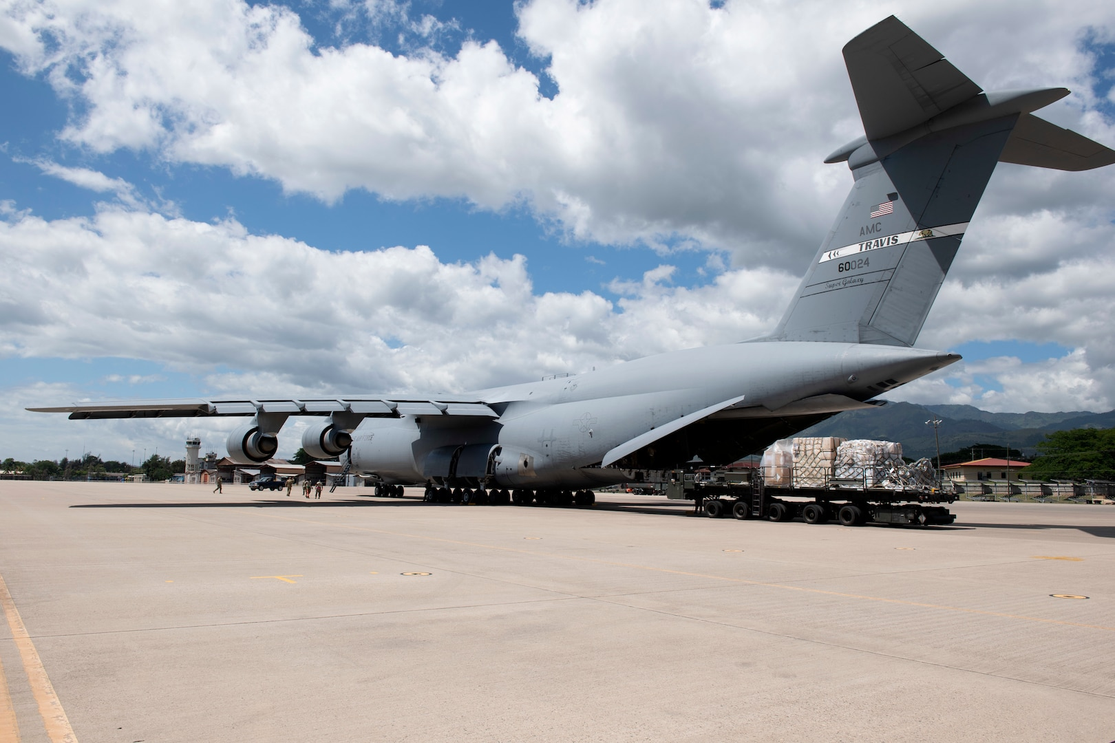 U.S. Airmen assigned to the 22nd Airlift Squadron off-load cargo from a C-5M Super Galaxy onto a K-loader July 18, 2020, at Soto Cano Air Base, Honduras. The aircrew delivered 58,000 pounds of cargo to Honduras for humanitarian relief to help with the COVID-19 pandemic, infrastructure and emergency services. (U.S. Air Force photo by Senior Airman Jonathon Carnell)