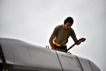 A photo of an Airman unstrapping an inert missile.