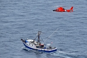 A Coast Guard aircrew medically evacuates a man from a fishing vessel operating 100 miles west of Coos Bay, Oregon, July 11, 2020. The aircrew hoisted the injured fisherman safely and transferred him to emergency medical services personnel. (U.S. Coast Guard photo by Petty Officer 3rd Class Ben Loy)