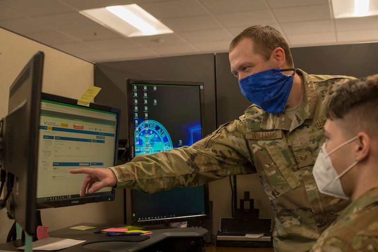 Staff Sgt. Wade Williams, left, 49th Comptroller Squadron special actions noncommissioned officer in charge, shows Staff Sgt. John Demko, 49th CPTS financial operations supervisor, how to navigate the new Comptroller Services Portal system, July 15, 2020, at the 49th CPTS on Holloman Air Force Base, N.M. Holloman members with 'us.af.mil' e-mail addresses can look forward to having items such as basic allowance for housing, hardship duty pay and clothing allowance taken care of through this new online program that begins July 27.  (U.S. Air Force photo by Senior Airman Collette Brooks)