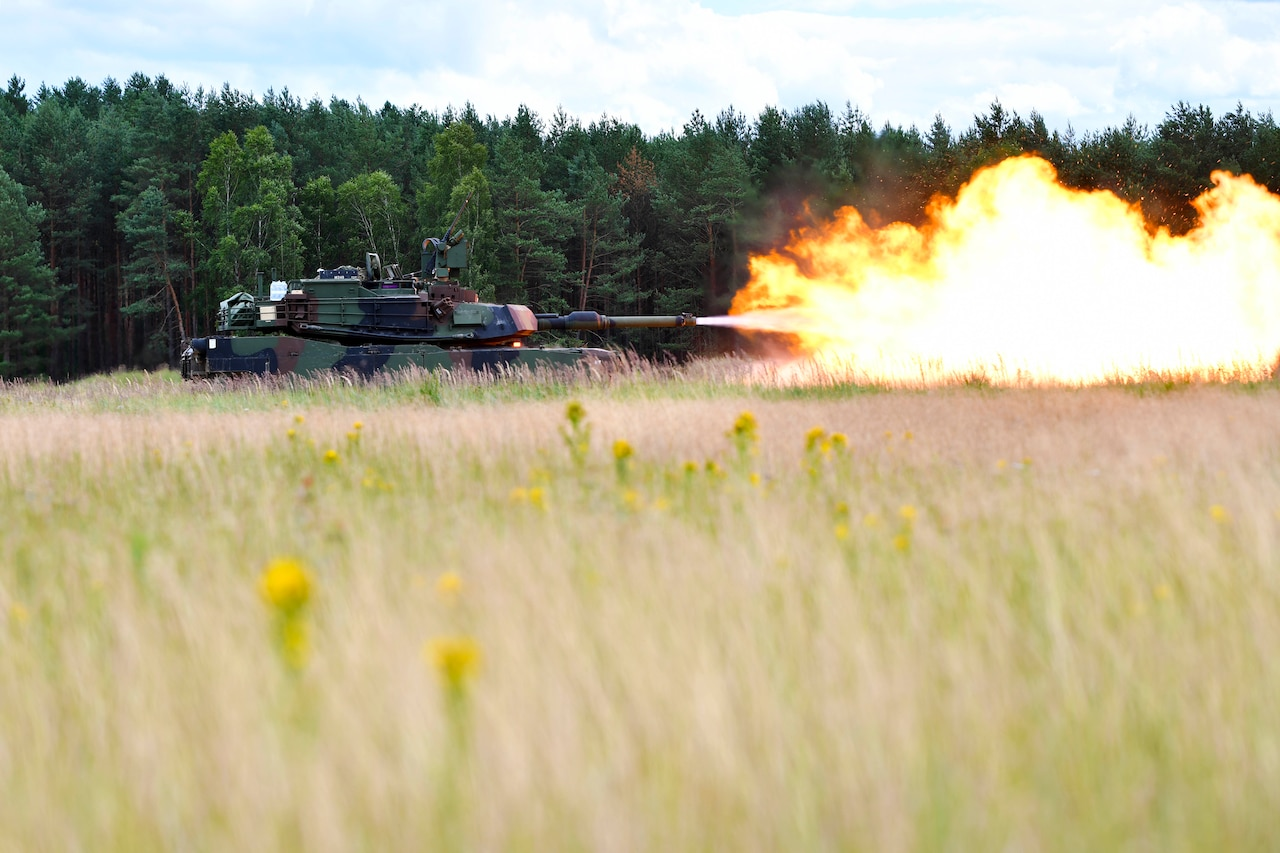 A tank fires a large blast in the middle of a field.