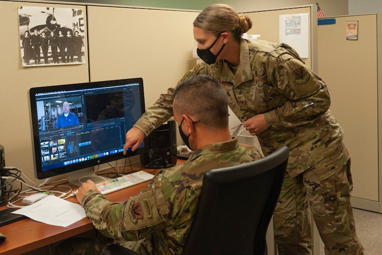 Photo of an Airman helping Chief Wilfong edit a video