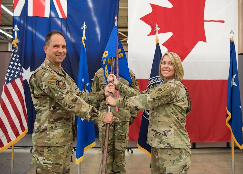 Col. Monique C. DeLauter, incoming Director, Combined Space Operations Center, and Commander, 614th Air Operations Center (right), receives the guidon from Maj. Gen. John E. Shaw, Commander, Combined Force Space Component Command and Space Operations Command (left)