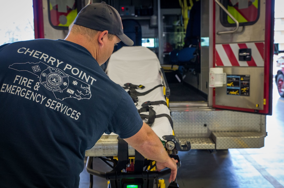 Dale Askew pulls out a stretcher from the back of an ambulance at Marine Corps Air Station Cherry Point, N.C., June 29.
