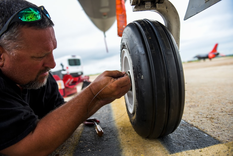 Michael Reeves with the 82nd Aerial Targets Squadron, contractor, works to replace the front landing tire on a QF-16 at Tyndall Air Force Base, Florida, July 9, 2020. The 82nd ARTS contractors fulfill a variety of different flight line technical skills including replacing old or malfunctioning landing gear. (U.S. Air Force photo by Staff Sgt. Magen M. Reeves)