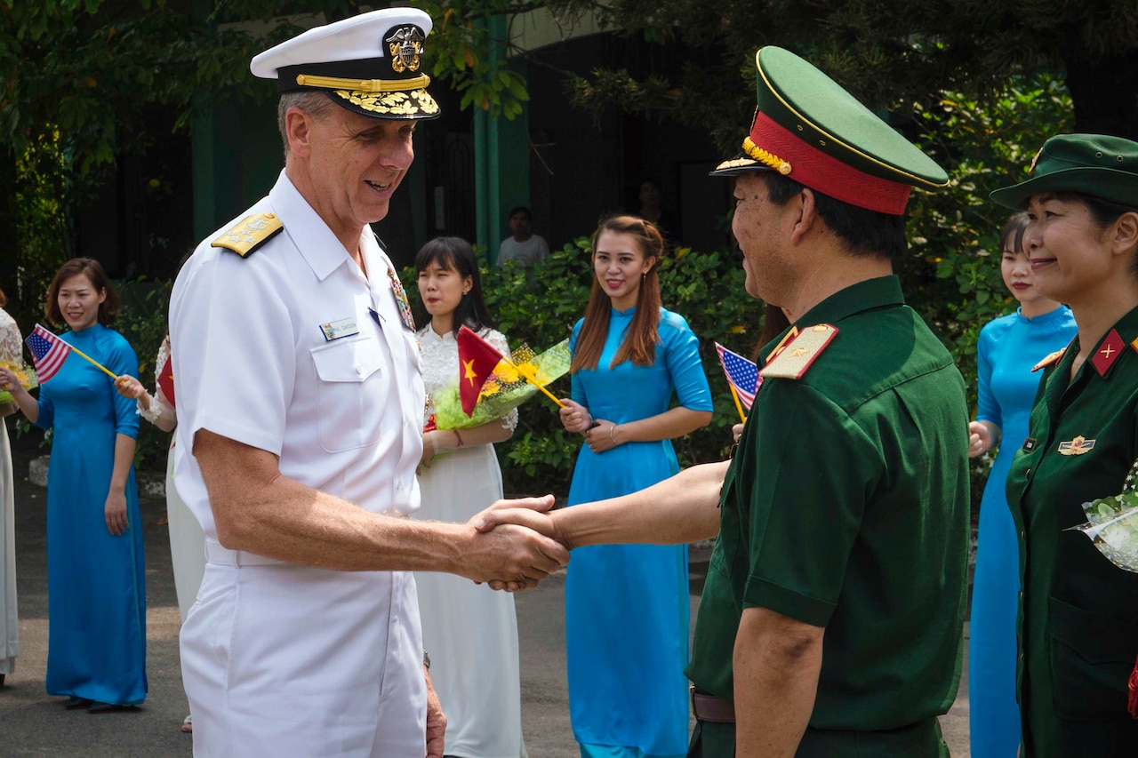 Two men dressed in military uniforms shake hands as others look on.