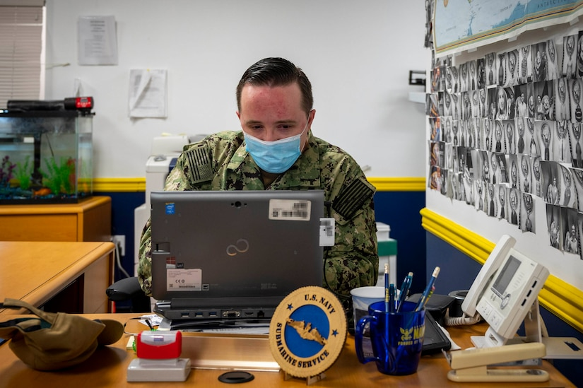 A sailor wearing a face mask works on a laptop.