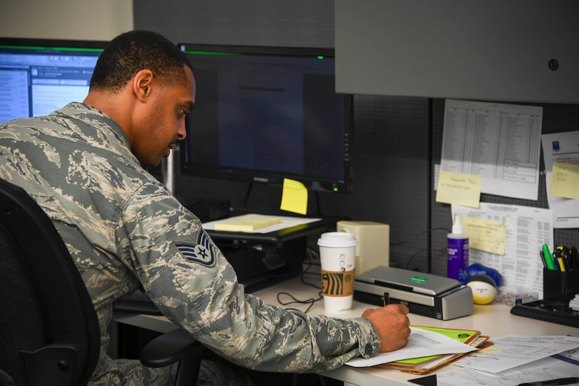 An airman sits at a desk during telework.