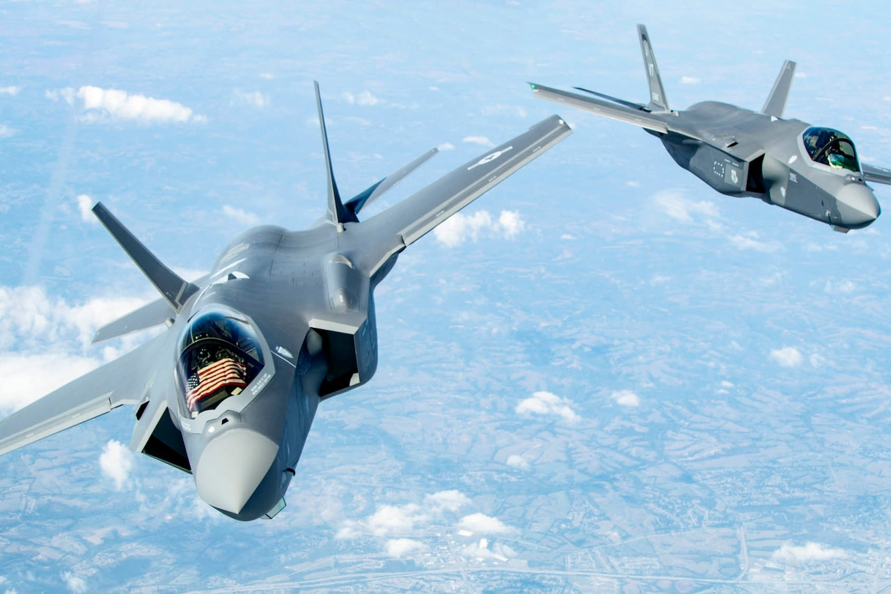 Two military fighter aircraft fly in formation.
