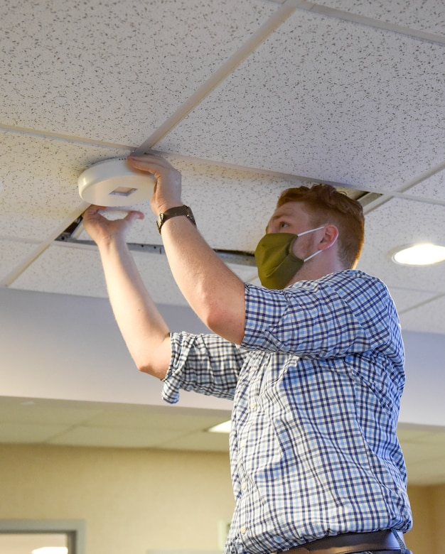 Jordan, a field engineer for FAR UV Technologies, installs an ultraviolet light in the 189th Operations Group ceiling July 16, 2020, at Little Rock Air Force Base, Ark. The UV lighting is environmentally-friendly and mercury-free.