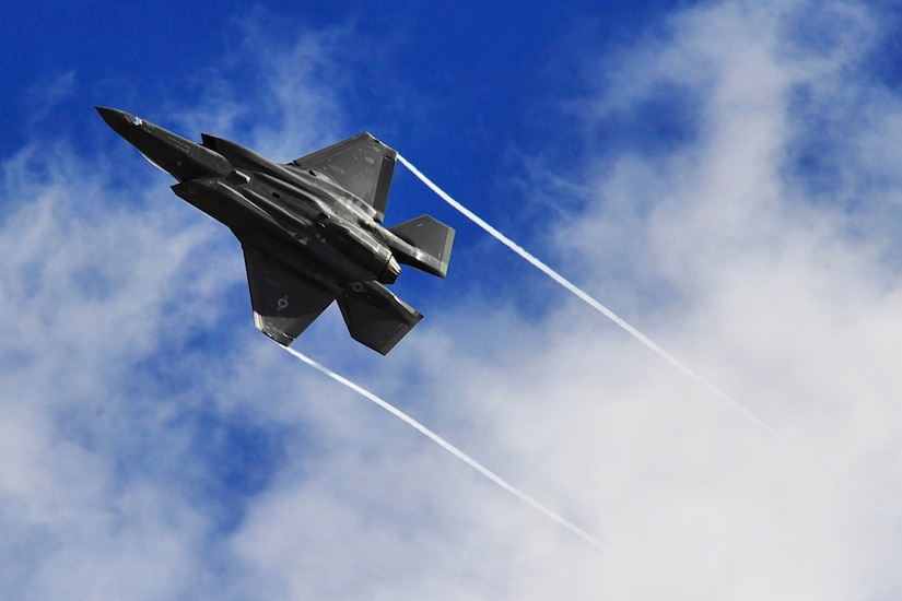 A fighter jet flies against clouds and a deep blue sky. Condensation trails from its wing tips.